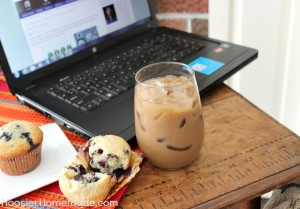 Close up photo of blueberry muffin next to an iced coffee