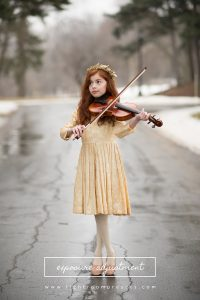 Red-headed girl playing the violin in the street