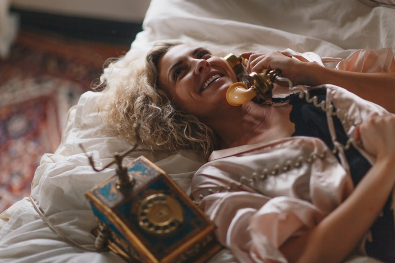 woman on bed with phone