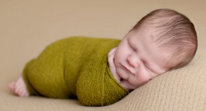 Newborn boy wrapped in a green swaddle