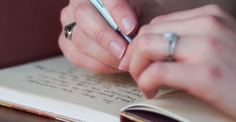 Close up of photographers hands writing in a book