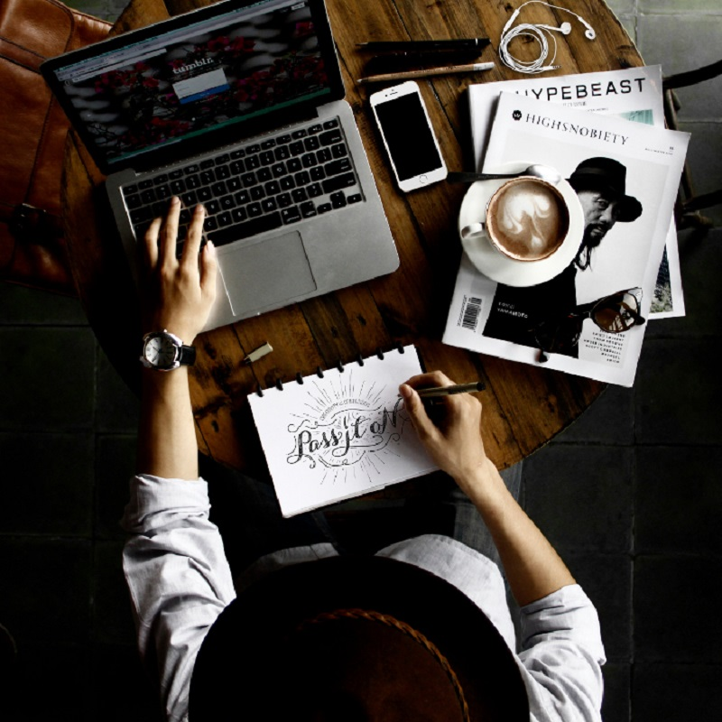 Woman drinking coffee working at a desk