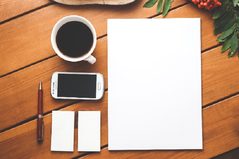 Coffee, cell phone, and blank pad of paper