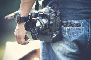 man carrying nikon camera