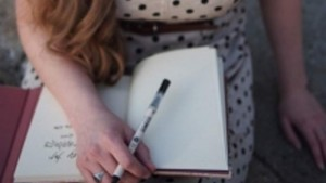 Photographer writing in a journal with pen and pad